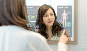 young woman checking a futuristic mirror with weather and health information